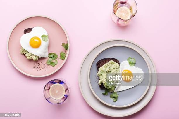 brunch on valentine's day,  avocado toasts with fried egg - crockery stock pictures, royalty-free photos & images