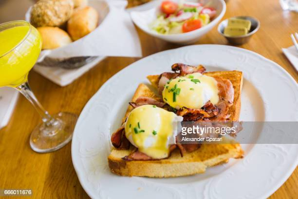 brunch with eggs benedict and mimosa cocktail served on the table - mimosa stock pictures, royalty-free photos & images