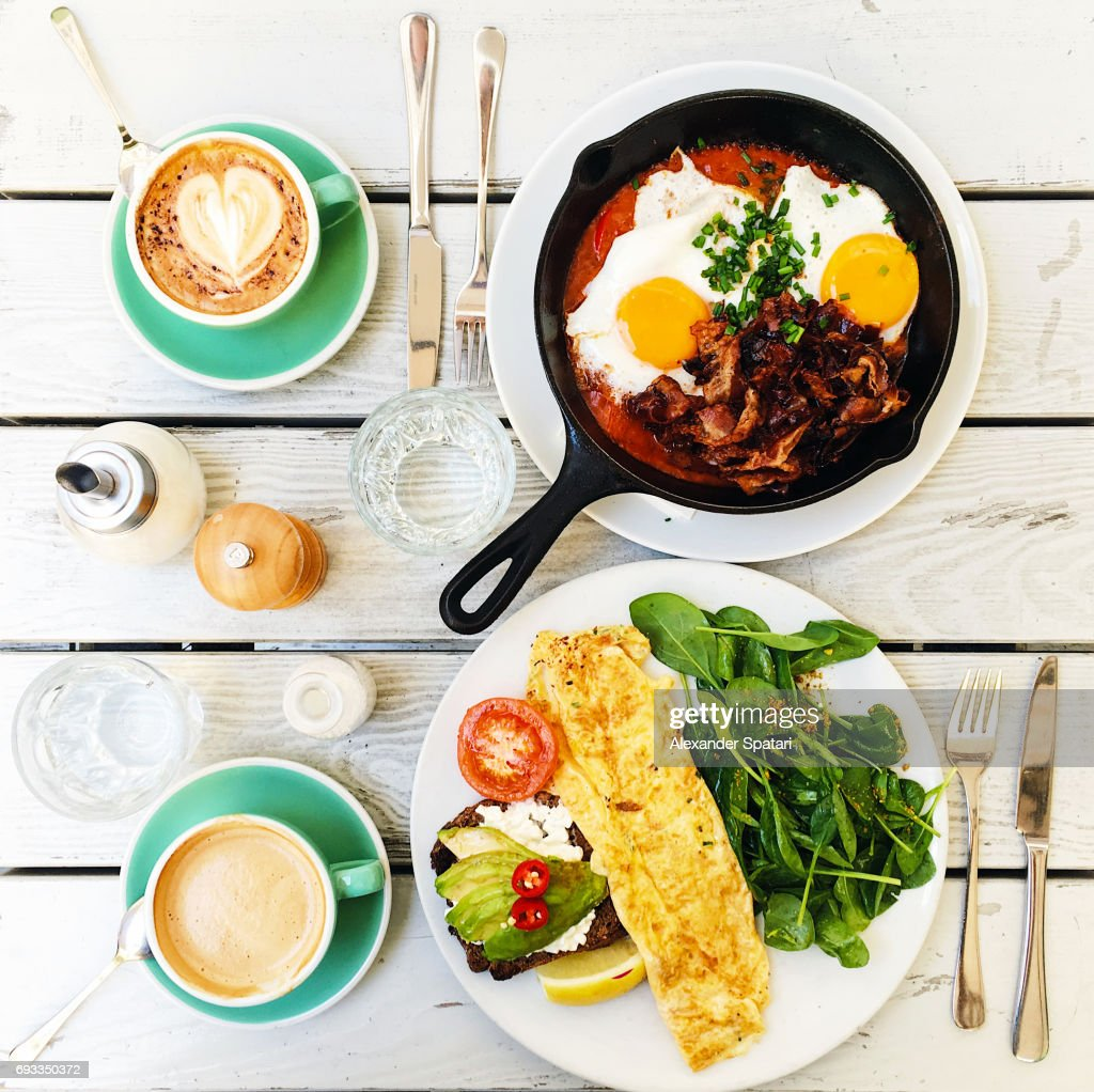 Brunch with fried eggs, bacon, omelet and avocado on toast served on the table, high angle view : Stock-Foto
