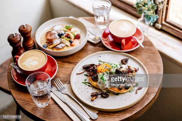 brunch with savoury pancakes and cottage cheese pancakes served with cappuccino - table stock pictures, royalty-free photos & images