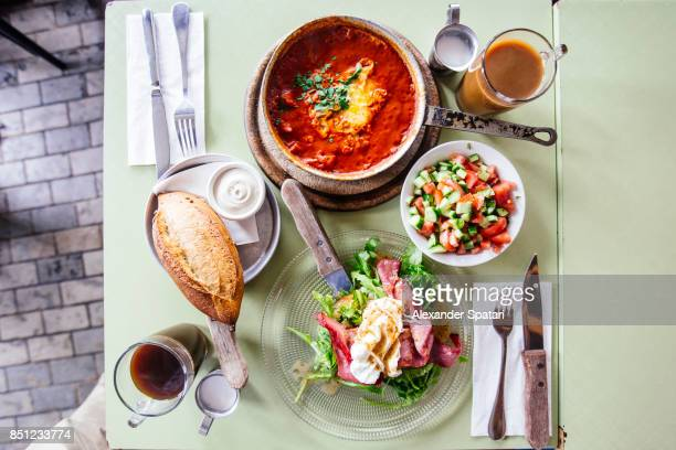 brunch with shakshuka in a skillet served with fresh bread, hummus, salad and beef salad with poached egg - tel aviv stock pictures, royalty-free photos & images