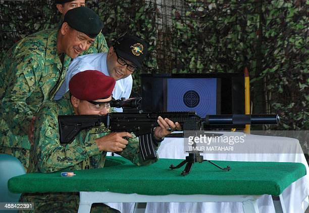 Brunei Crown Prince General AlMuhtadee Billah test fires Indonesianmade assault rifle during a visit at PT Pindad Indonesia's state owned defense...