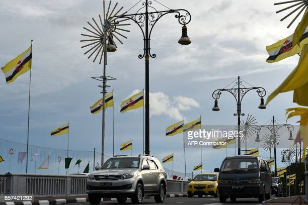 Brunei's national flags are flown along a street in Bandar Seri Begawan on October 4 2017 Brunei will mark its Sultan's Hassanal Bolkiah 50th jubilee...