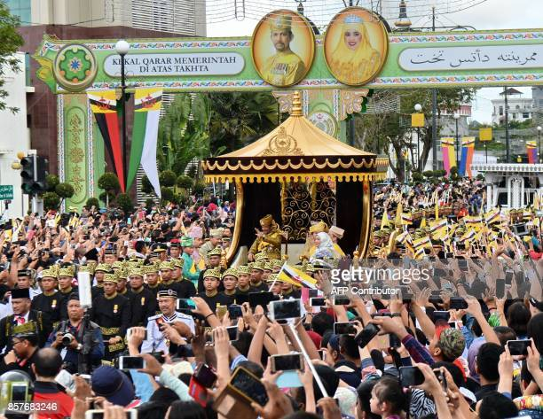 Brunei's Sultan Hassanal Bolkiah and Queen Saleha wave from the royal chariot during a procession to mark his golden jubilee of accession to the...