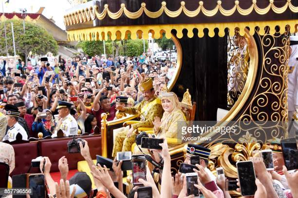 Brunei's Sultan Hassanal Bolkiah and Queen Saleha wave to people as they march through Brunei's capital Bandar Seri Begawan on Oct 5 to mark 50 years...