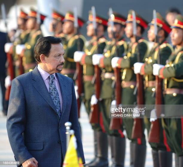 Brunei's Sultan Hassanal Bolkiah walks past an honour guard upon his arrival at Wattay airport to attend the ninth Asia-Europe summit in Vientiane on...