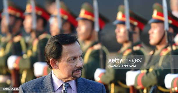Brunei's Sultan Hassanal Bolkiah walks past an honour guard upon his arrival at Wattay airport to attend the ninth AsiaEurope summit in Vientiane on...