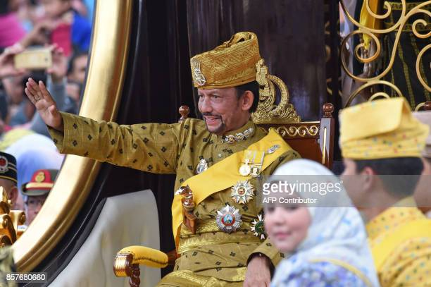 Brunei's Sultan Hassanal Bolkiah waves from the royal chariot during a procession to mark his golden jubilee of accession to the throne in Bandar...