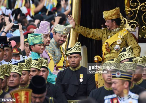 Brunei's Sultan Hassanal Bolkiah waves while Crown Prince AlMuhtadee Billah Prince Abdul Malik and Prince Abdul Wakeel look on from the royal chariot...
