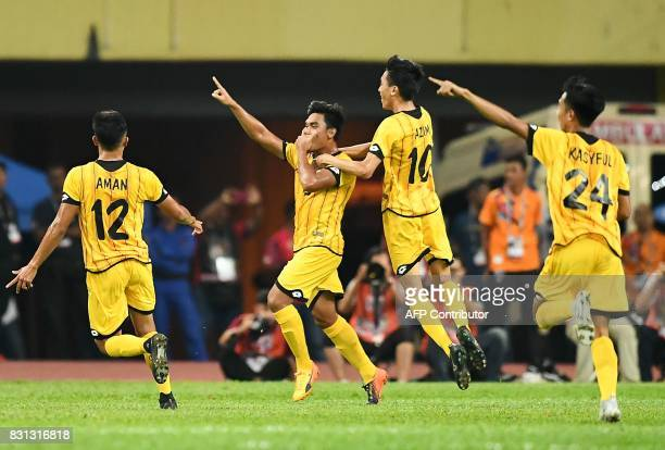 Brunei's Zulkhairy Hady Razali celebrates with his teammates after scoring a goal against Malaysia during their men's football Group A match at the...