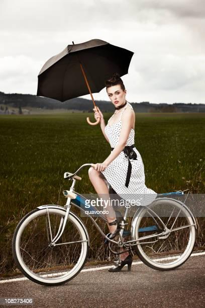 Brunette modelo de modas en bicicleta retención de una sombrilla, espacio de copia