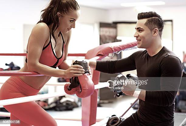 Brunette female at a gym with personal trainer