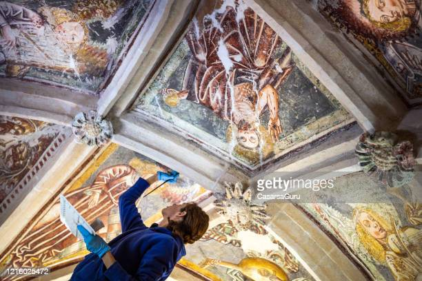 brunette female painter restoring ceiling paintings with paintbrush in catholic chapel - stock photo - history stock pictures, royalty-free photos & images