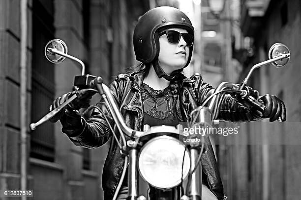 brunette female posing on vintage motorbike in city centre - women black and white motorcycle stock pictures, royalty-free photos & images