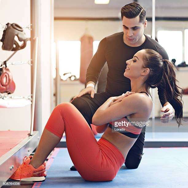 Brunette female working out at a gym with personal trainer