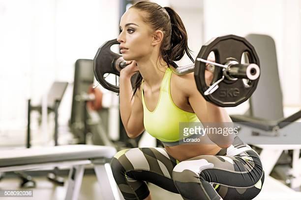 Morena mulher treinar no ginásio com pesos