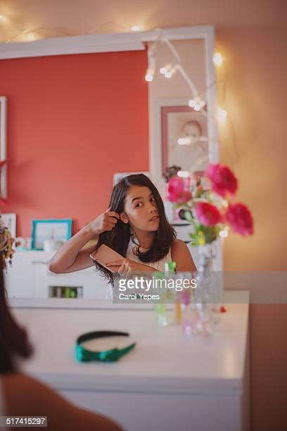 Brunette girl combing her hair