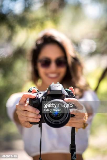 brunette girl holding camera out and smiling - camera girls stock photos and pictures