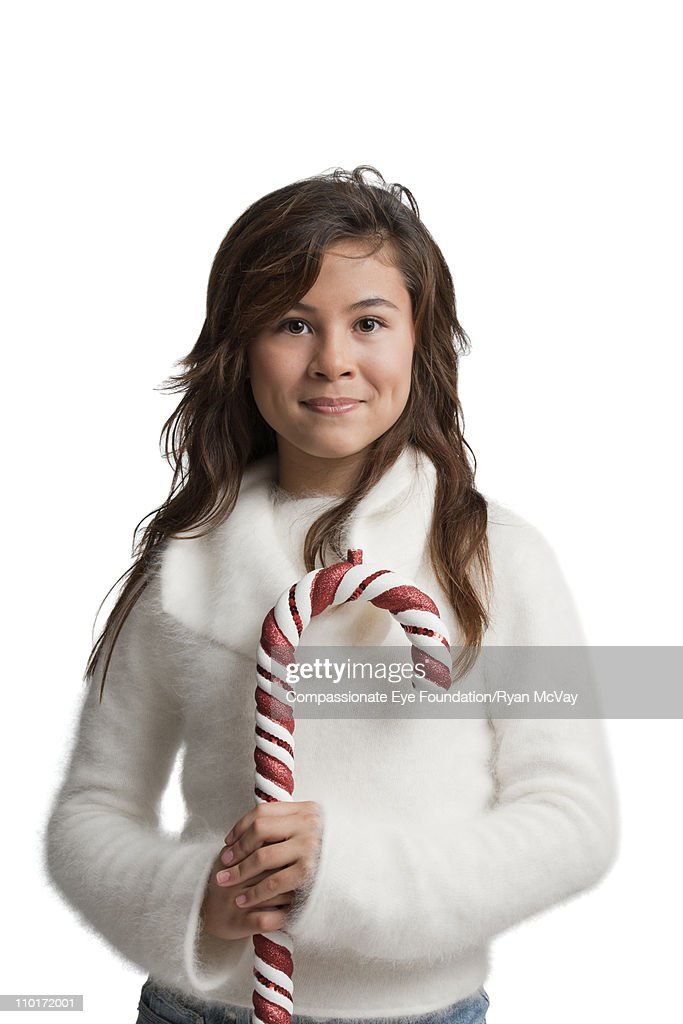 Brunette girl in white holding a candy cane : Stock Photo