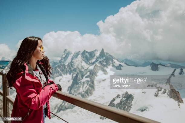 brunette girl looking over snow landscape.top of the alps - aiguille de midi stock photos and pictures