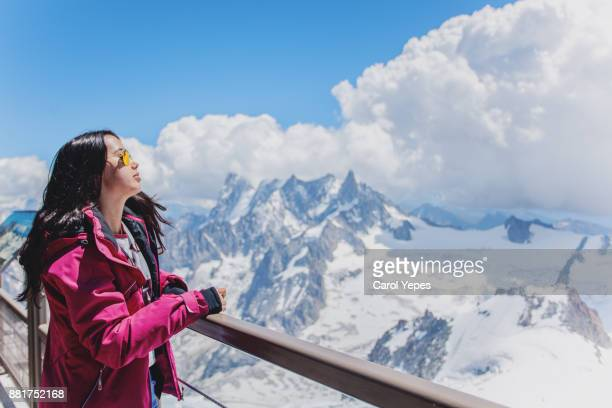 brunette girl looking over snow landscape.Top of the alps