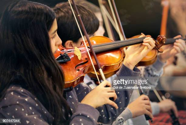 brunette girl playing the violin in a children's music band - arte, cultura e espetáculo imagens e fotografias de stock