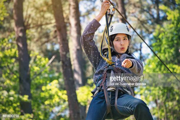 brunette girl with helmet and harness sliding on a zip line - truth or dare stock pictures, royalty-free photos & images