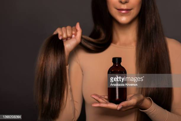 brunette girl with long straight and shiny hair. beauty skin woman holding her strong and healthy hair and oil or shampoo bottle over grey background. cosmetic hair beauty salon concept. - brown hair stock pictures, royalty-free photos & images