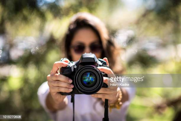 brunette holding camera - digital camera stock pictures, royalty-free photos & images