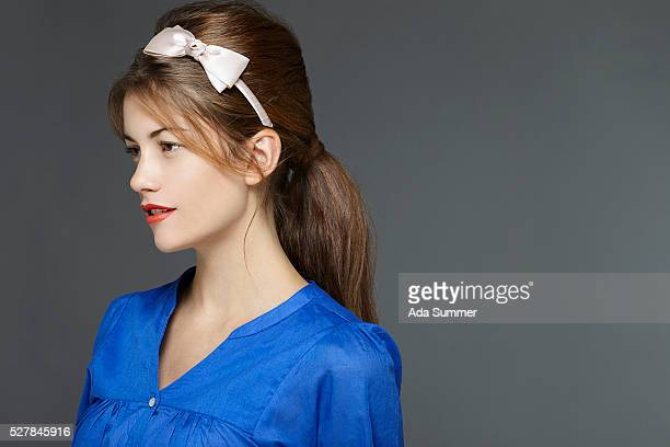 brunette in a blue blouse with a pink alice band - hair bow stock pictures, royalty-free photos & images