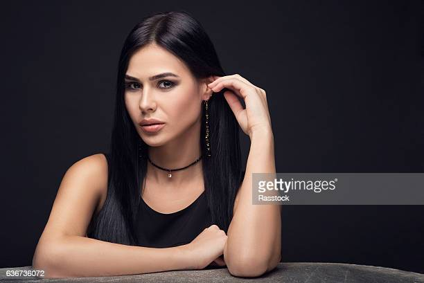 brunette luxury model in dark dress and jewelry on dark