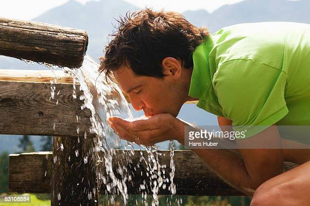 Man drinking water from fountain, side view
