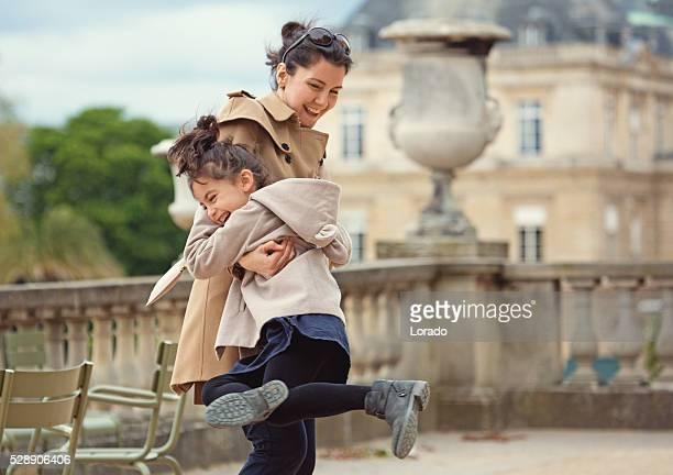 Brunette mère et fille embrassant dans Parc après-midi de printemps à Paris