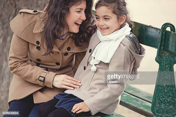 Brunette mother daughter sitting in Paris park on spring afternoon
