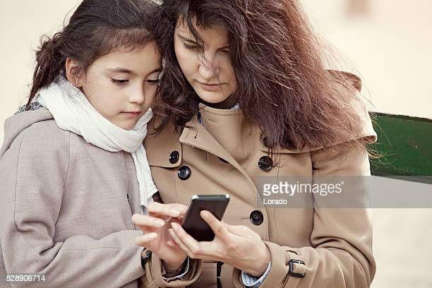 brunette mother daughter using smartphone in paris on spring afternoon - premium access stock pictures, royalty-free photos & images