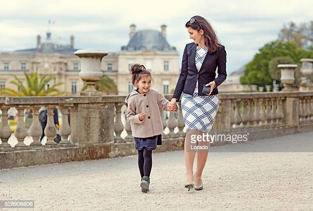 Brunette mother daughter walking in Paris park on spring afternoon