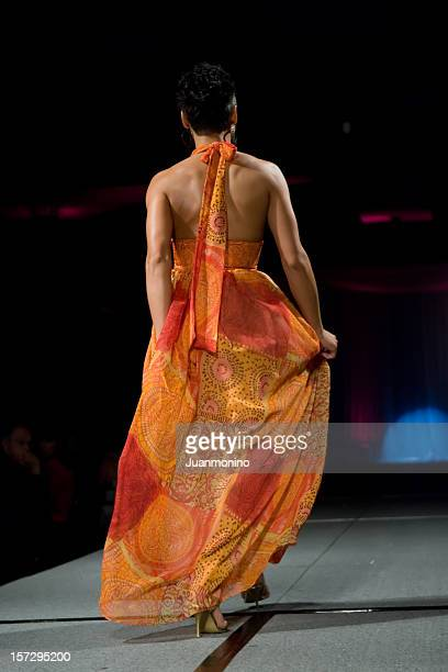 a brunette runway model in an orange dress from behind. - fashion collection stock photos and pictures
