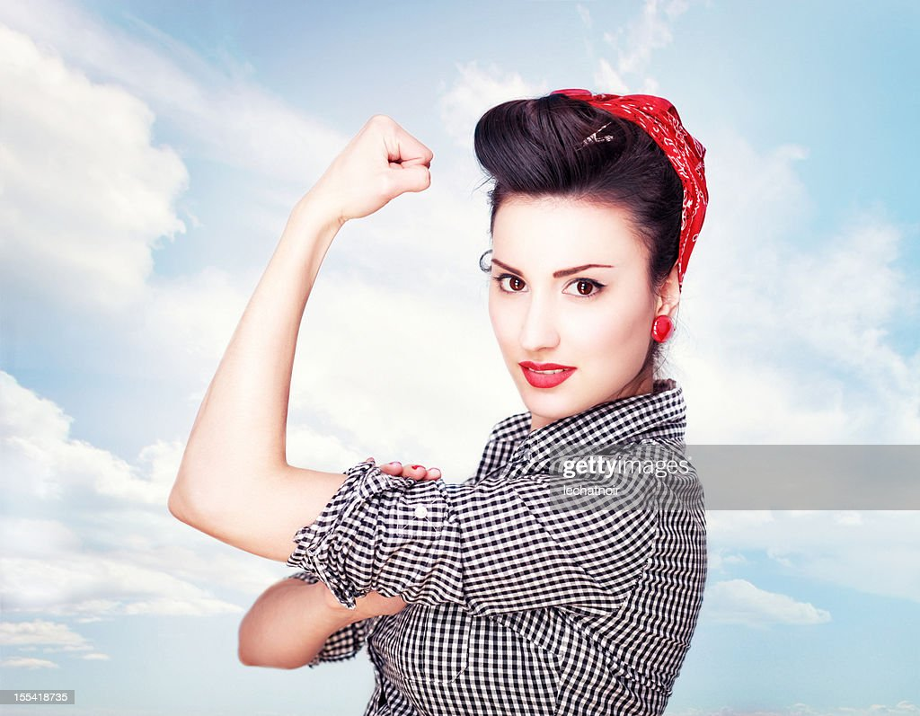 Brunette impressionante um famoso Rosie Riveter pose : Foto de stock