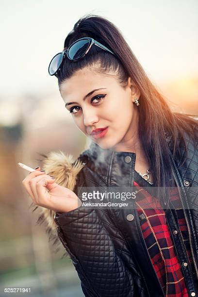 brunette stylish teenage girl smoking cigarette at sunset - beautiful women smoking cigarettes stock photos and pictures