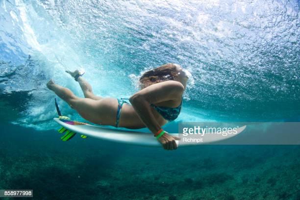 Brunette surfer girl duck dives