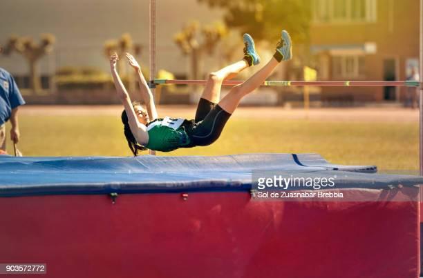 Brunette teen girl doing high jump in a sunny day