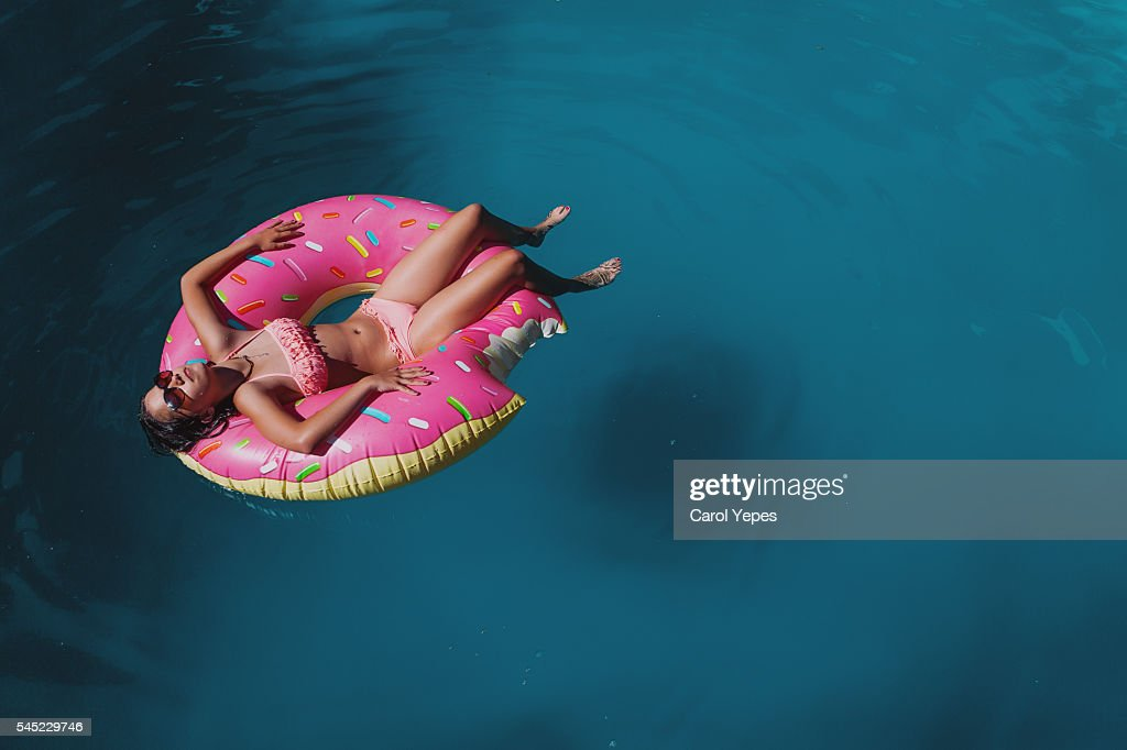 brunette teen in donuts inflatable ring. : Stock Photo