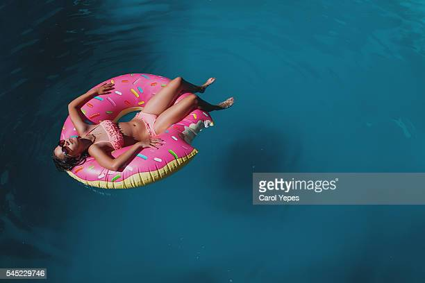 brunette teen in donuts inflatable ring. - standing water stock pictures, royalty-free photos & images