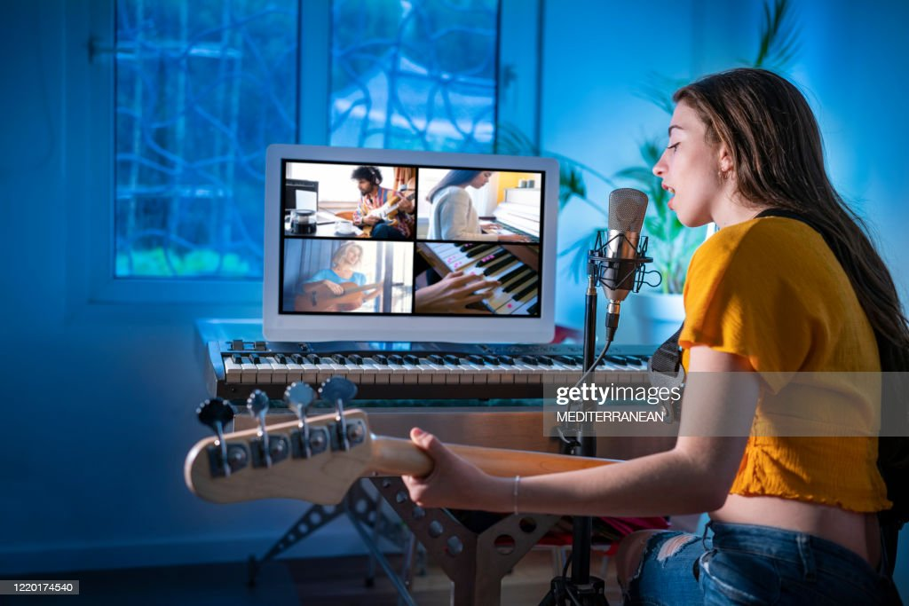 Brunette teen musician singer girl singing and playing bass guitar teleconference : Stock Photo