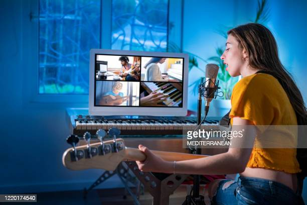 brunette teen musician singer girl singing and playing bass guitar teleconference - musician stock pictures, royalty-free photos & images