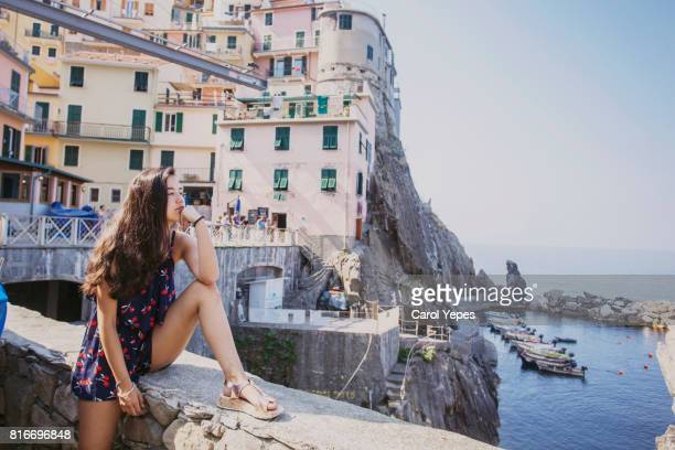 brunette teenager sitting  looking at Manarola,Cinque Terre, Italy