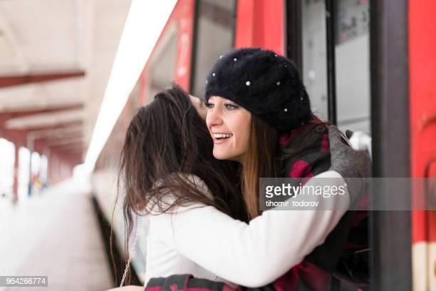 Brunette traveler giving friend hug after winter break