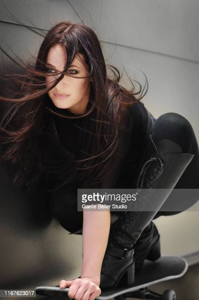 brunette with long hair riding a skateboard - ブーツイン ストックフォトと画像
