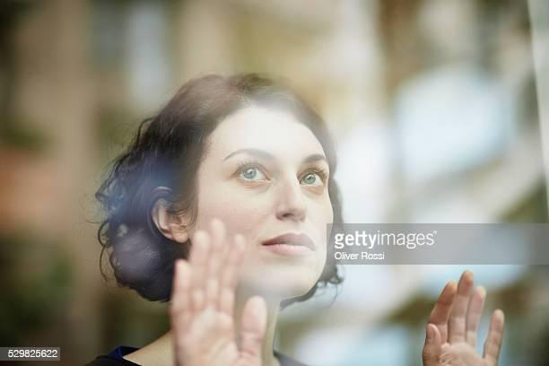 brunette woman behind windowpane looking up - esperar fotografías e imágenes de stock