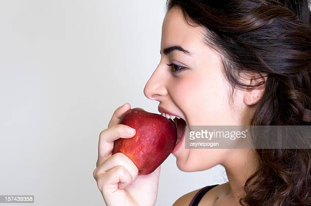 Brunette woman biting into a red apple